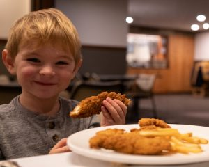 child eating chicken fingers